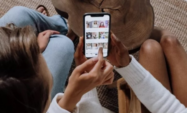Two people showing each other photographs with their mobile phones.