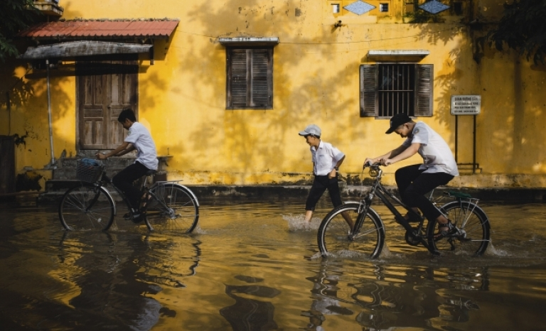 Children cycling on a street flooded by rain.