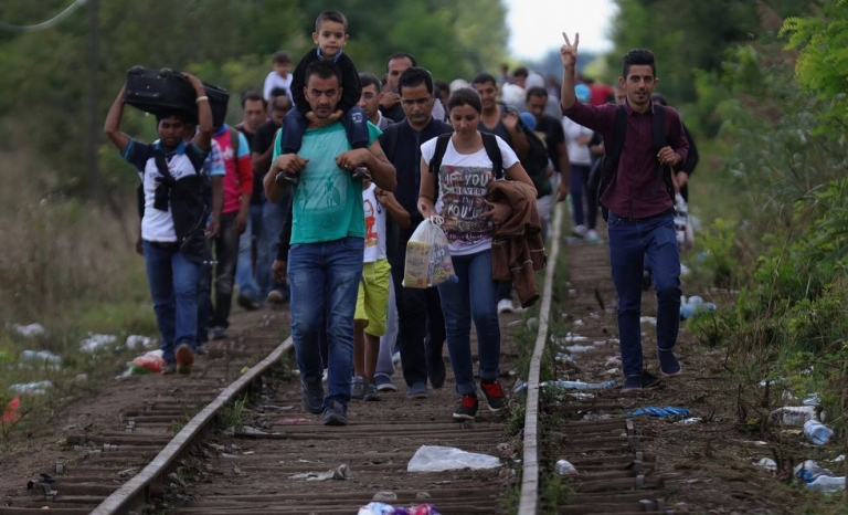 A group of refugees walk from Serbia to Austria through the train tracks - Photo: getty images