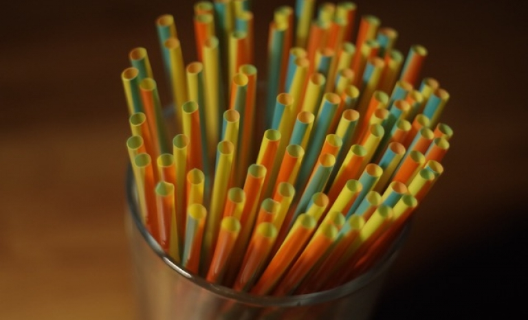 Colorful plastic straws on a glass container. Photo: Pexels