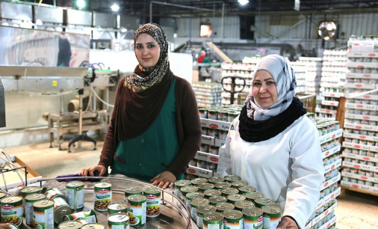 Two refugees working at a food factory / Photo: Bea Arscott, Flickr